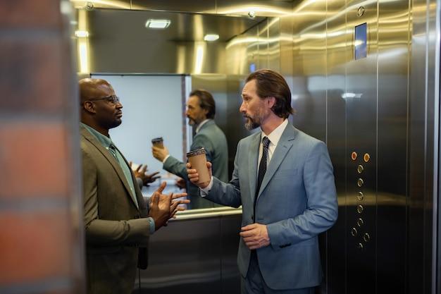 Stojąc w windzie. siwy mężczyzna rozmawiający z kolegą stojąc rano w windzie