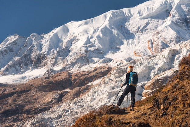 Stojąca młoda kobieta z plecakiem na górskim szczycie i patrząc na piękne góry i lodowiec o zachodzie słońca