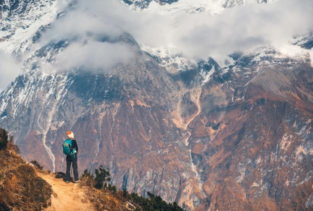 Stojąca młoda kobieta z plecakiem na ścieżce na wzgórzu i patrząc na piękne wysokie góry o zachodzie słońca.