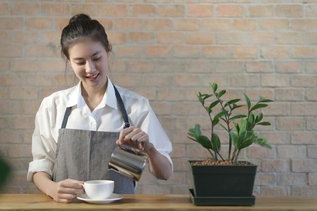 Stojąca młoda śliczna azjatycka kawowa barista dziewczyna nalewa kawę do filiżanki na stole