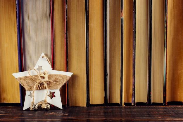 Stojąca na półce z książkami gwiazda dekoracji świątecznych.