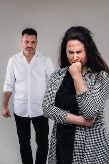 Stojąca za nią kobieta bita przez męża i patrząca na nią agresywnie. przemoc domowa.