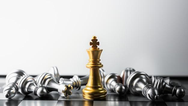 Stojące szachy złotego króla spotykają pokonanych wrogów.