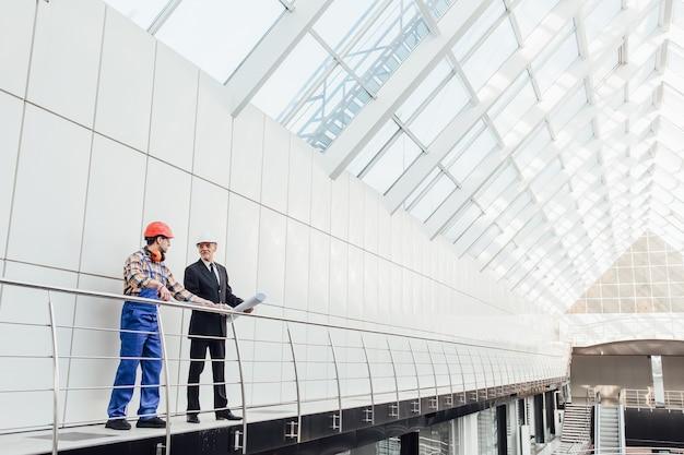 Stojący inżynierowie przemysłowi w niebieskich kamizelkach i hełmach