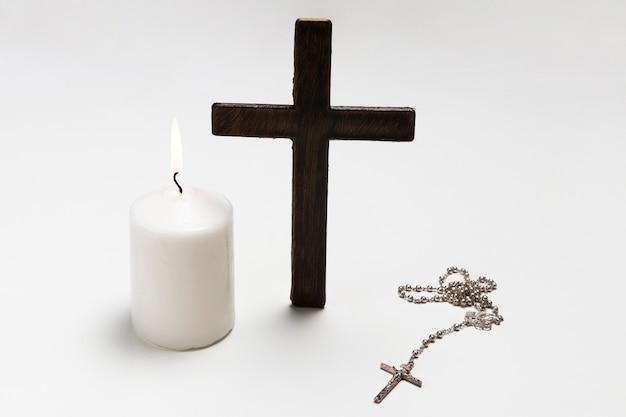 Stojący krzyż z zapaloną świecą i naszyjnikiem