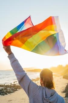 Stojący mężczyzna podniósł tęczową flagę lgbt do nieba