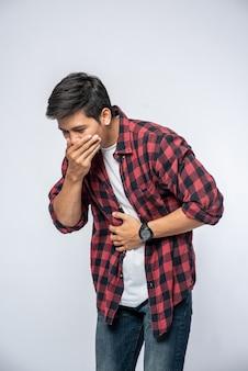 Stojący mężczyzna z bólem brzucha połóż ręce na brzuchu i zakryj usta.