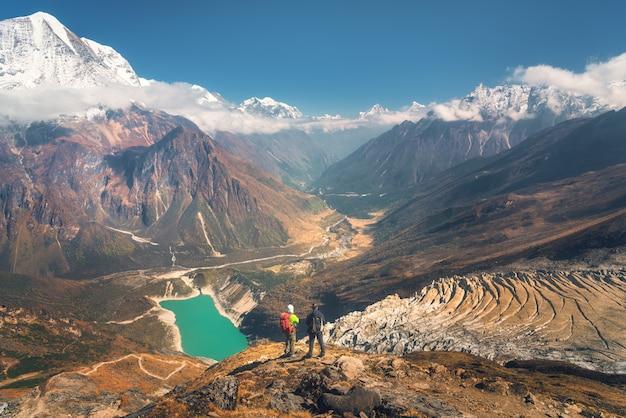 Stojący mężczyźni z plecakami na szczycie góry i patrząc na piękną górską dolinę o zachodzie słońca.