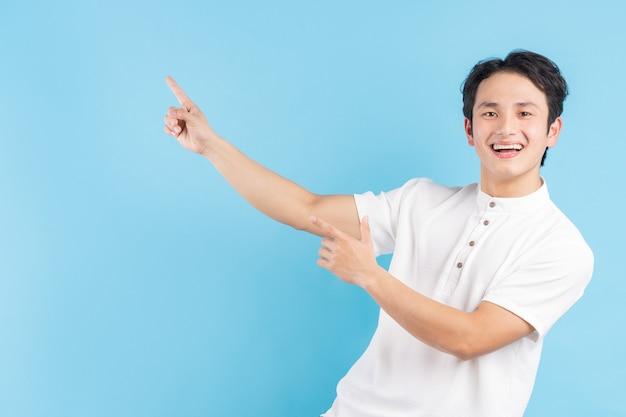 Stojący na boku młodzieniec z radosnym wyrazem twarzy wskazał ręką w bok