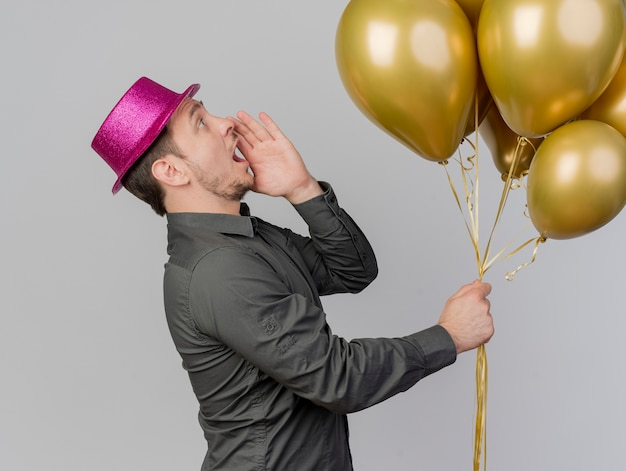 Stojący w widoku profilu młody partyjny facet ubrany w różowy kapelusz trzymając balony wzywając kogoś na białym tle