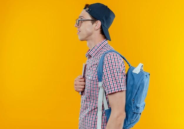 Stojący w widoku profilu młody uczeń chłopiec ubrany w tylną torbę i okulary i czapkę na białym tle