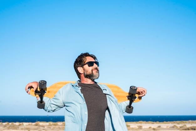 Stojący wolny brodaty przystojny dorosły mężczyzna z długą deską skate, ciesząc się wolnością i zdrowym stylem życia - niebieski ocean i niebo w tle - koncepcja aktywnych ludzi