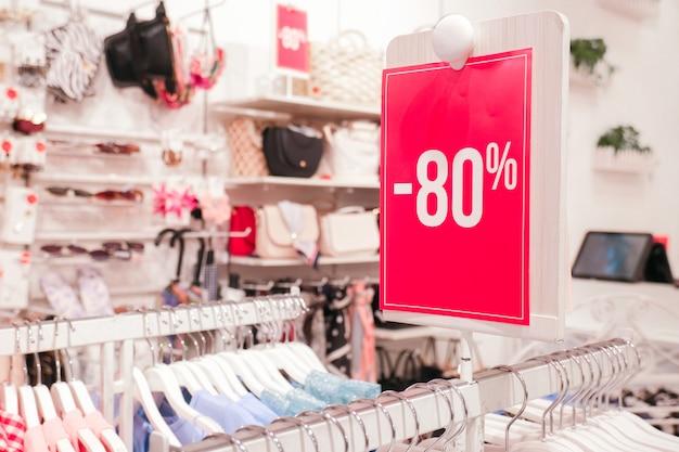 Stojak czerwony 80 procent zniżki w sklepie. wieszaki na ubrania