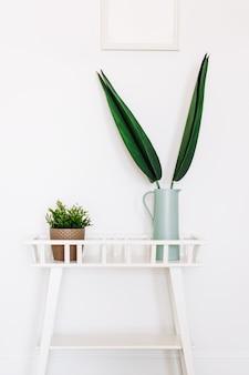 Stojak na kwiaty z rośliną doniczkową i wazonem z zielonymi liśćmi na tle białej ściany.