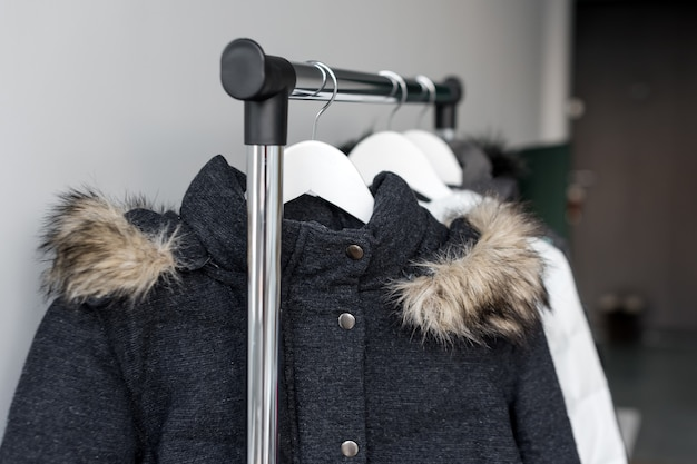 Stojak na wieszaki z ciepłymi kurtkami. zimowe kurtki z futrzanym kołnierzem wiszą na białych drewnianych wieszakach.