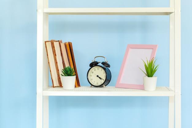 Stojak z białego metalu z książkami o niebieską ścianę