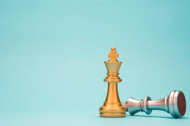 Stojak ze złotymi szachami króla i upadłymi srebrnymi szachami króla. zwycięzca konkursu biznesowego i koncepcji planowania strategii marketingowej.