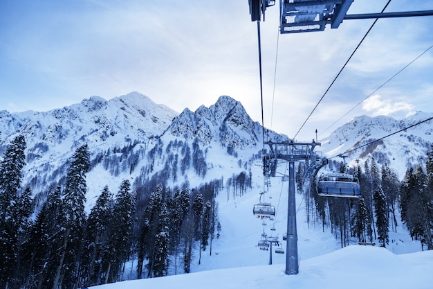 Stoki narciarskie i kolejka linowa w górach kaukazu pokryte śniegiem. piękny zimowy dzień. zajęcia na zewnątrz dla ludzi. ośrodek narciarski rosa khotor w rosji.
