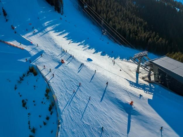Stoki narciarskie w zalesionych górach. stacja wyciągu narciarskiego. słoneczna pogoda. widok z lotu ptaka