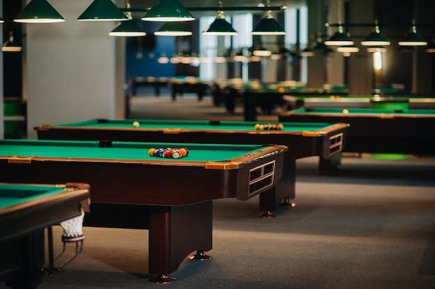 Stół bilardowy z zieloną powierzchnią i kulkami w klubie bilardowym. gra w bilard.
