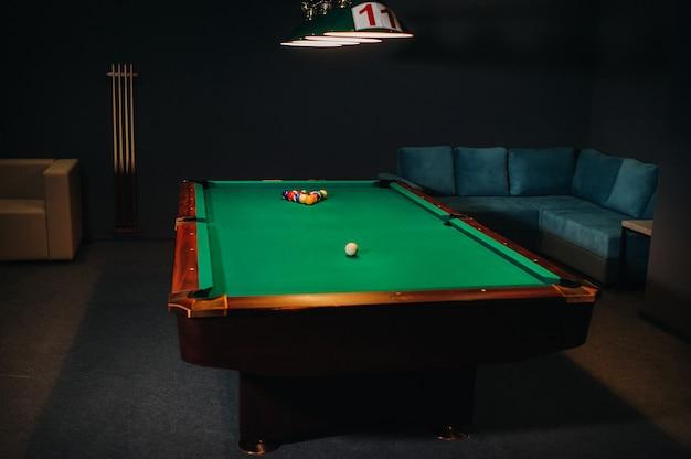 Stół bilardowy z zieloną powierzchnią i kulkami w klubie bilardowym.