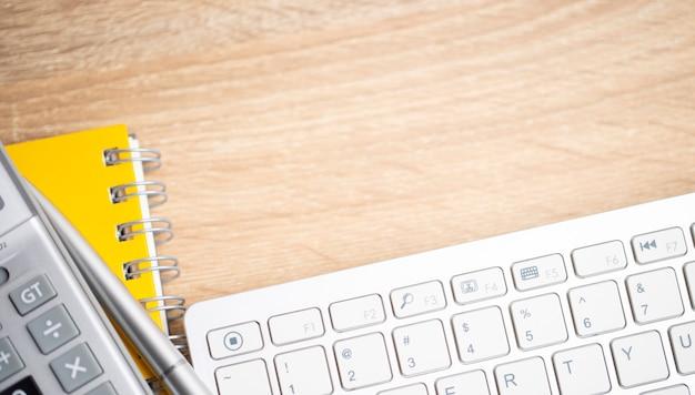 Stół biurkowy z klawiaturą, kalkulatorem i żółtą książką na brązowym stole z drewna