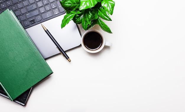 Stół biurowy w miejscu pracy z laptopem, filiżanką kawy, notatnikiem i zieloną rośliną. widok z góry z miejscem na kopię