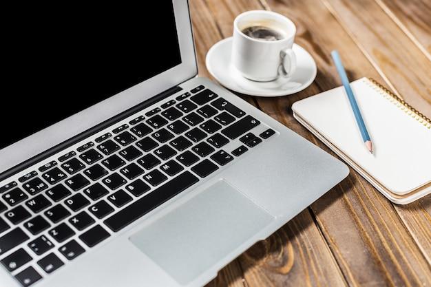 Stół biurowy z bliska, otwórz laptopa i filiżankę kawy