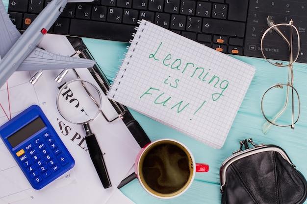 Stół biurowy z długopisem, keaboard, filiżanką kawy, okularami i notatnikiem. nauka w notatniku to świetna zabawa.