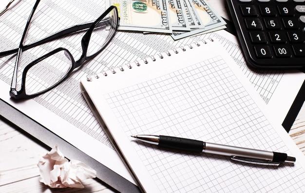 Stół biurowy z kalkulatorem, notatnikiem, długopisem, okularami i banknotami dolarowymi. stylowe miejsce pracy. pomysł na biznes
