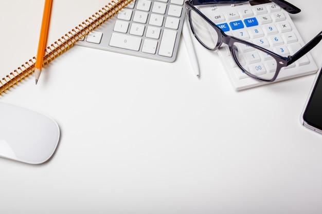 Stół biurowy z klawiaturą komputerową, materiałami eksploatacyjnymi, kalkulatorem, długopisem, okularami