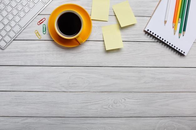 Stół biurowy z komputerem, dostawami, filiżanką kawy i kwiatem. odosobniony
