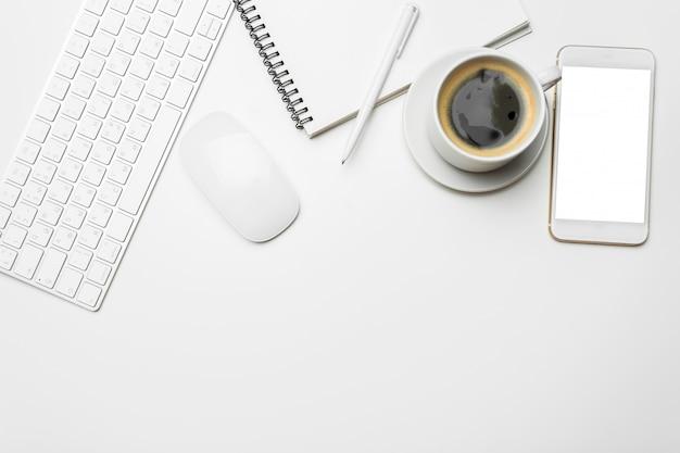 Stół biurowy z komputerem, materiałami eksploatacyjnymi, filiżanką kawy
