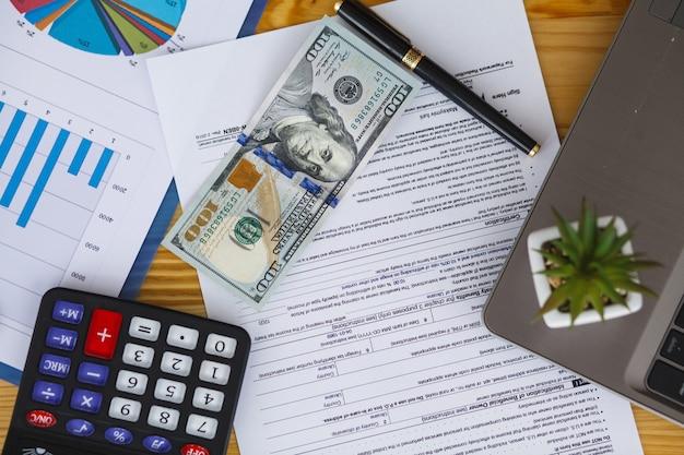 Stół biurowy z komputerem, materiałami eksploatacyjnymi i roślinami