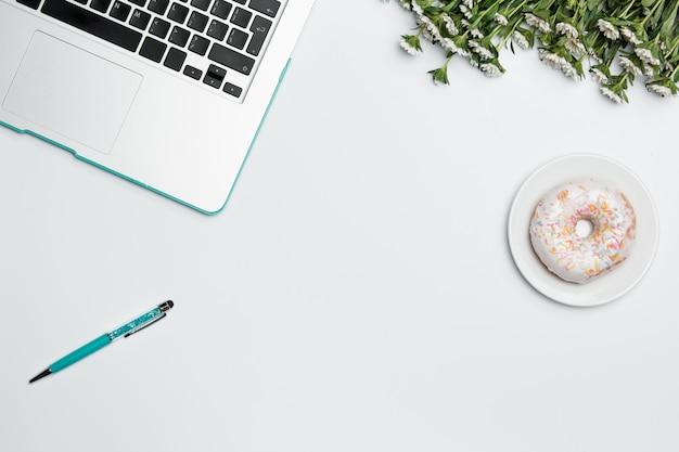 Stół biurowy z komputerem, materiałami eksploatacyjnymi, kwiatami