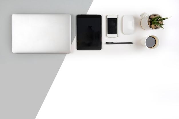 Stół biurowy z laptopem, notebookiem, cyfrowym tabletem i smartfonem na dwóch ba tonowych