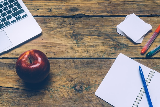 Stół biurowy z laptopem, piórami, notatnikiem i jabłkiem.