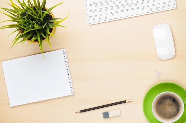 Stół biurowy z notatnikiem, komputerem, filiżanką kawy i kwiatem. widok z góry z miejscem na kopię
