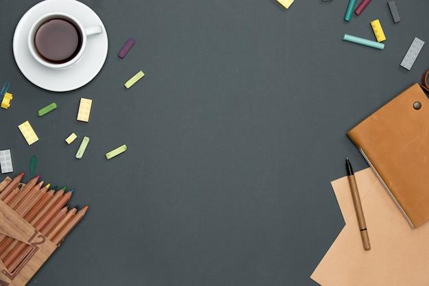 Stół biurowy z ołówkami, materiałami eksploatacyjnymi i filiżanką