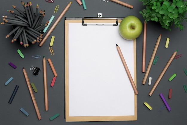 Stół biurowy z ołówkami, materiałami i kwiatami