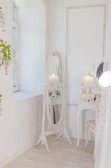 Stół buduarowy w stylu vintage z lustrem i kwiatami. biały jasny pokój. obraz pionowy. luksusowe wnętrze.