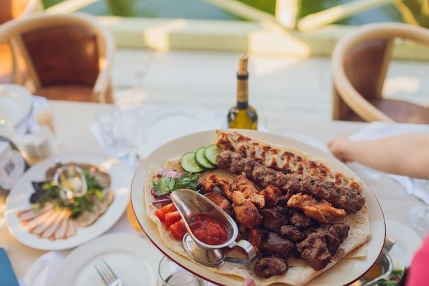 Stół bufetowy recepcji z burgerami, zimnymi przekąskami mięsnymi i sałatkami