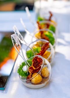 Stół bufetowy z zimnymi przystawkami i aperitifami. nowoczesny design talerzy kulowych. selektywne skupienie. ścieśniać.