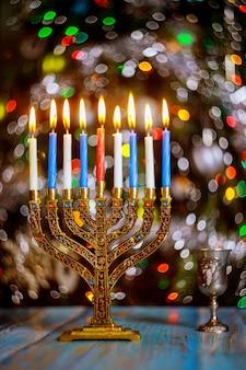 Stół chanuka z menorą i płonącymi świecami na błyszczącej powierzchni z niewyraźnymi kolorowymi światłami