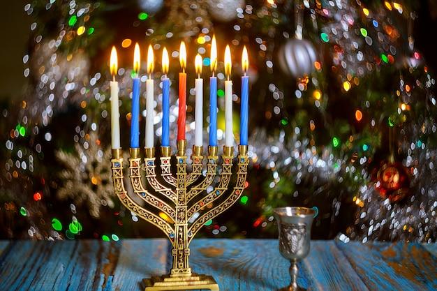 Stół chanuka z menorą i płonącymi świecami na błyszczącej powierzchni z rozmytymi kolorowymi światłami