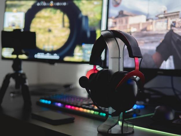 Stół dla graczy z sprzętem do gier, myszą, klawiaturą, zestawem słuchawkowym i podkładką pod mysz na czarnym tle stołu.
