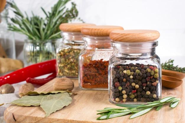 Stół do gotowania z przyprawami w szklanych słoikach i ziołach. na białej powierzchni
