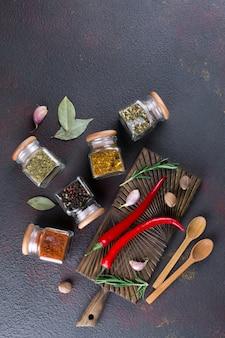 Stół do gotowania z przyprawami w szklanych słoikach i ziołach. na ciemnej powierzchni