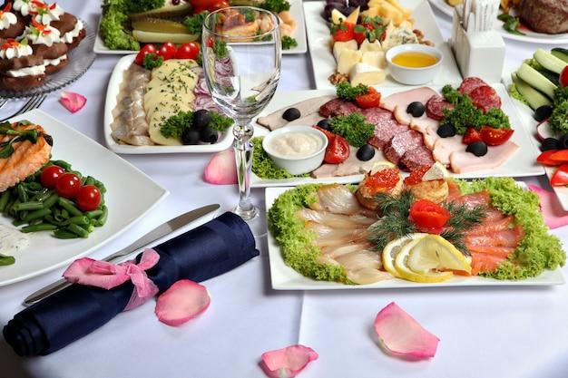Stół do jadalni ze świątecznymi dekoracjami, z przystawkami mięsnymi i rybnymi.