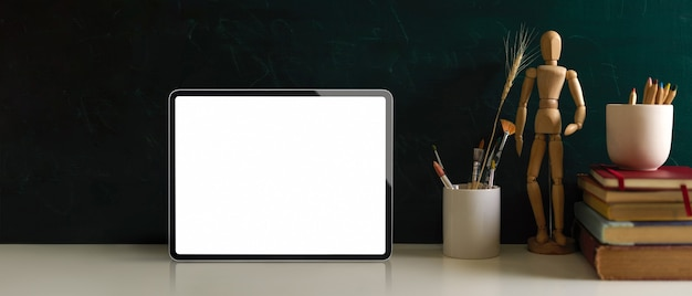 Stół do nauki z makietami książek cyfrowych na tablecie i elementami szkolnymi